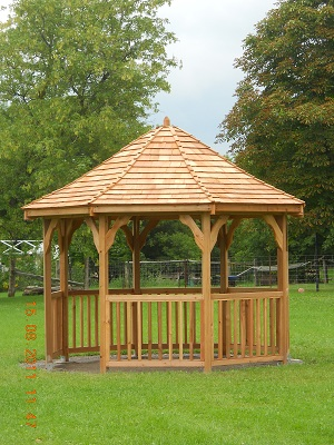 wooden gazebo in a grassy park with trees behind