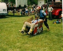 Person pushing another man in a cardboard firetruck