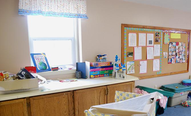 childrens pay area with corkboard covered in images