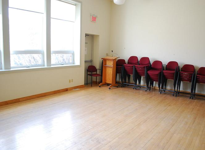 chairs stacking against wall in a large room with hardwood flooring