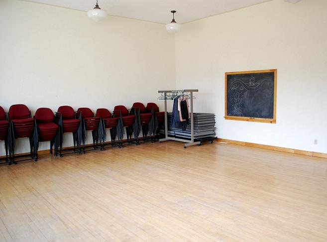 Chairs stacked against the wall in large room with hardwood flooring