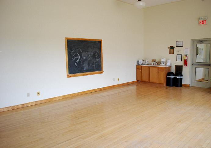 large open room with chalkboard and hardwood flooring