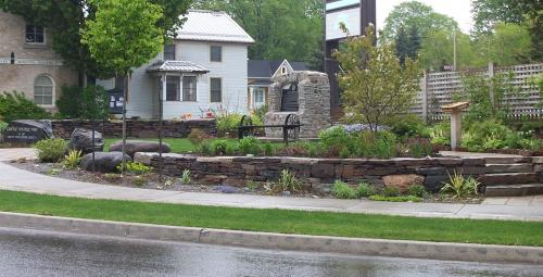 Picture of nice garden and low stone wall infront of house in the rain