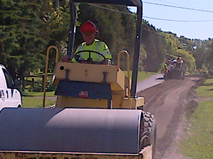 Man on road paver smoothing the road