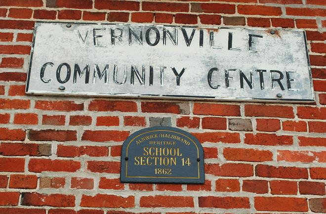 sign on brick wall that says Vernonville Community center